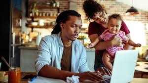 man at laptop, woman holding baby standing next to him